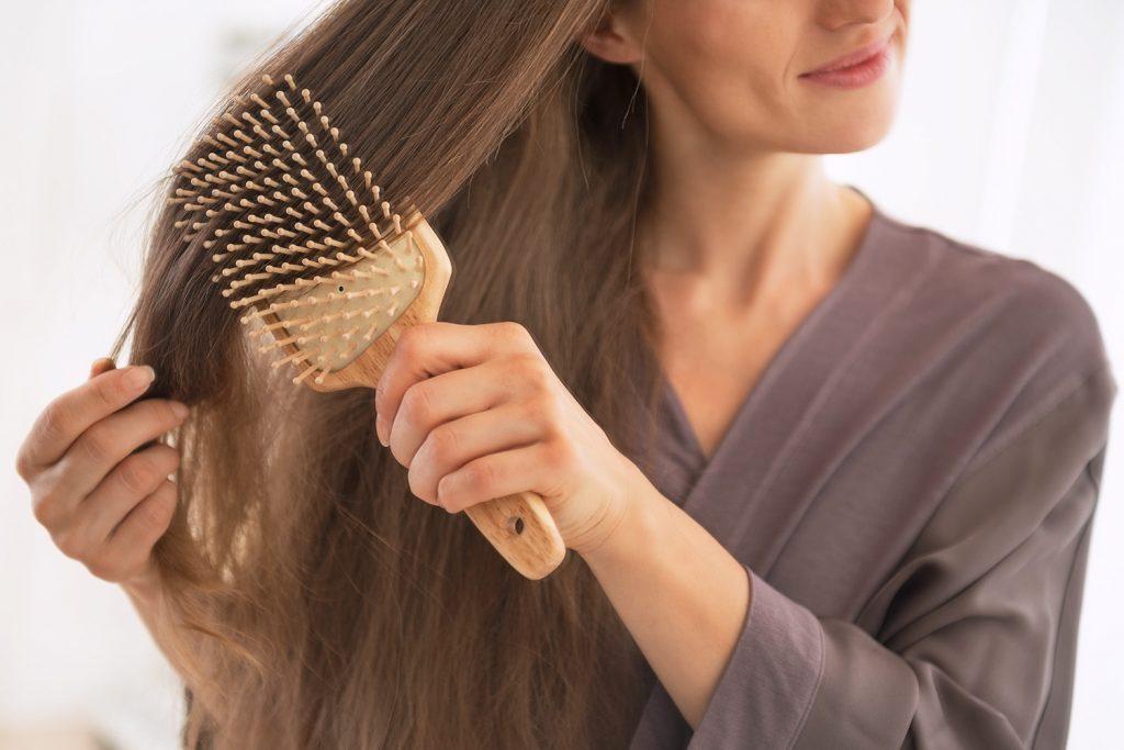 Paní si češe své zdravé vlasy.