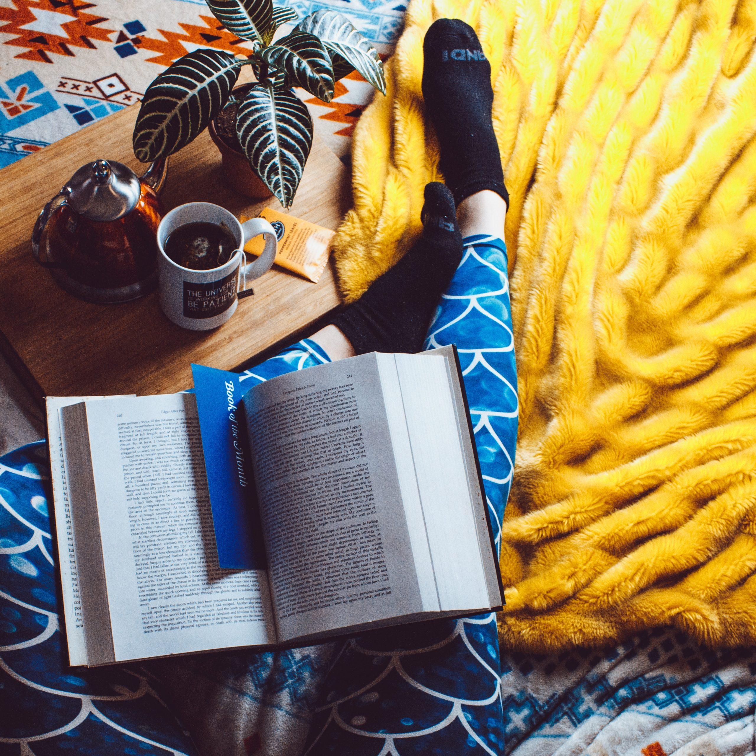 žena sedí na zemi, na klíně má knihu, vedle sebe podnos s čajem