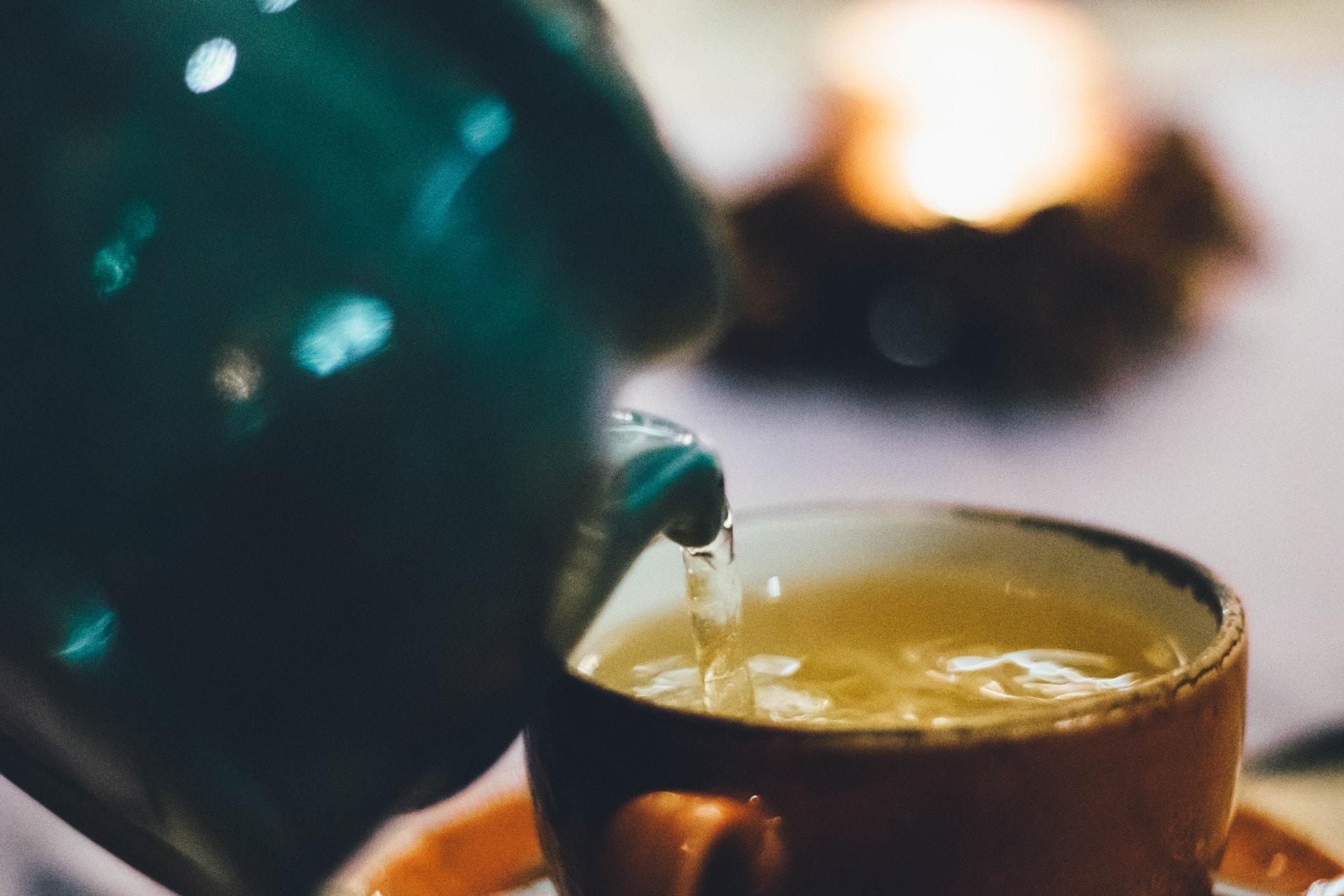 Hrnek, do kterého se lije čaj