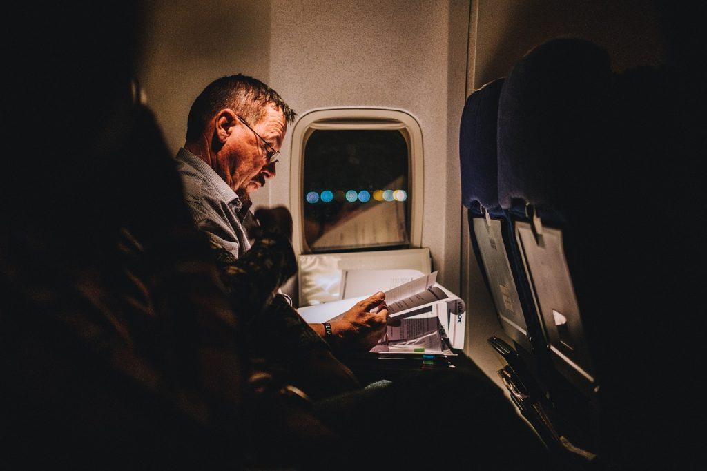 starší muž si čte v noci v letadle